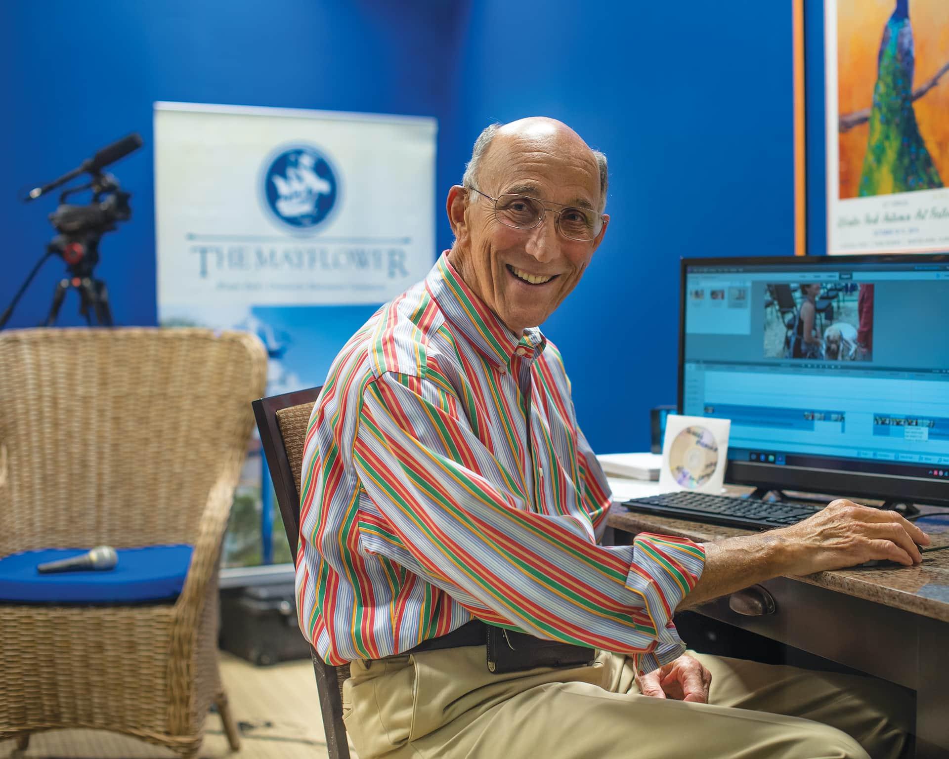 man sitting at a computer smiling
